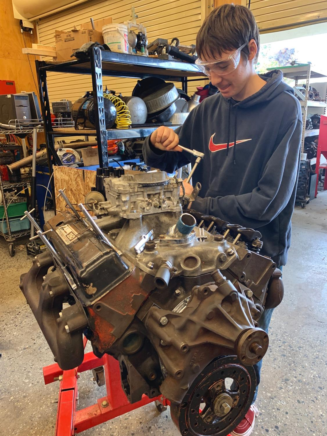 Joseph Newman (9) takes off the rocker-arms of an engine.